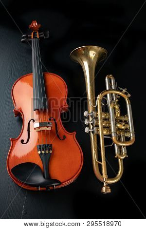 A New Shining Violin And An Old Trumpet On A Dark Table. Musical Instruments, Stringed And Wind.