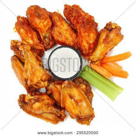 Spicy Chicken Wings with carrots, celery and ranch over white.