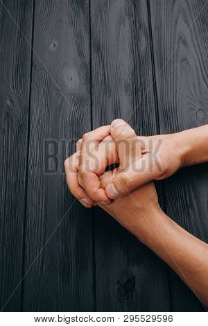 Interlocked Fingers, White Male Hands Interlocked On Black Rustic Wood Table Close Up. Top View. A M