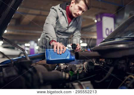 Man pouring oil in blue bottle in car with open hood
