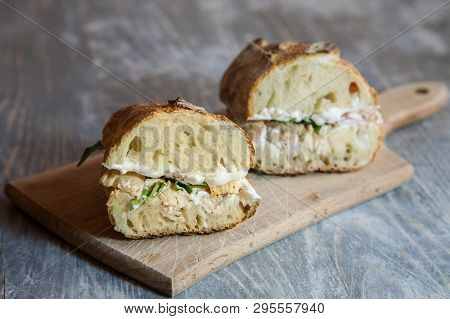 Chicken Sanwdich With Cream Cheese In A French Baguette, Cut In Two, With Some Slices Of Rucola Sala