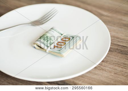 Money Lying On The Plate With Fork. Dollars Photo. Greedy Corruption Concept. Bribe Idea