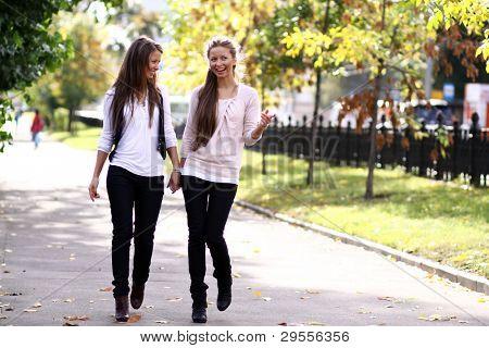 Fashionable girls twins walk in the street