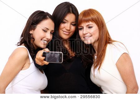 Three attractive young women take their picture on a phone