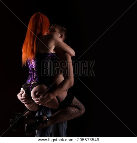 Redhead Sexy Cabaret Dancer In Lingerie And Corset Hugging Ordinary Man In Strip Club On A Dark Back