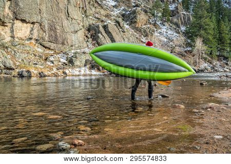 paddler carrying inflatable whitewater kayak on a shore of mountain river in early spring - Poudre River above Fort Collns, Colorado