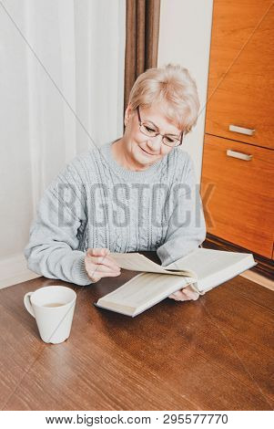 Senior woman is reading book on the table and drinking coffee, in home.