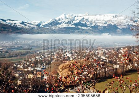 Town Of Vaduz The Capital Of Liechtenstein, Fog Above The River And Snow Mountains Of Switzerland Ov