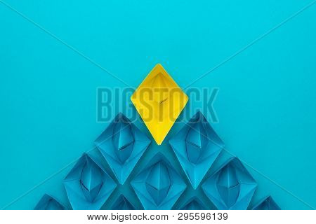 poster of yellow paper ship ahead of blue ones leadership concept. flat lay photo of leadership over blue back. top view of race with winning ship leadership metaphor. minimalist conceptual image of leadership
