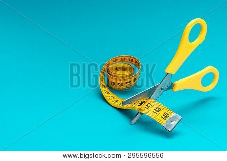Scissors Cutting Mesuring Tape On Turquoise Blue Background. Scissors Cutting Yellow Mesuring Tape D