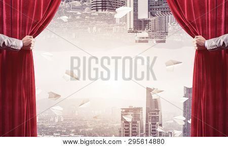 Hands Of Businessman Opening Red Velvet Curtain And Cityscape At Background
