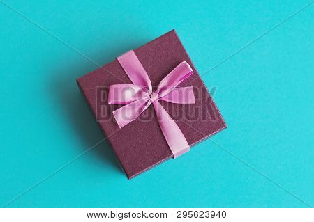 Small Purple Gift Box With Pink Ribbon On Turquoise Background. Present For Anniversary, Birthday, N