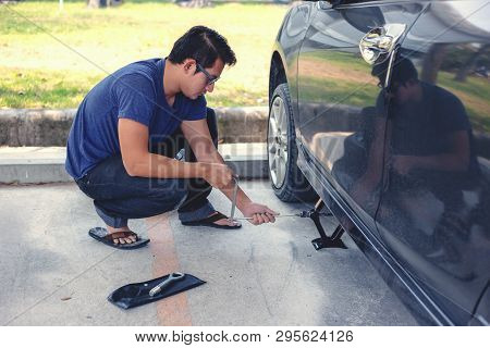 Hands Using Hydraulic Jack - Car Maintenance Concept. Car Tire Changed For Maintenance In Garage