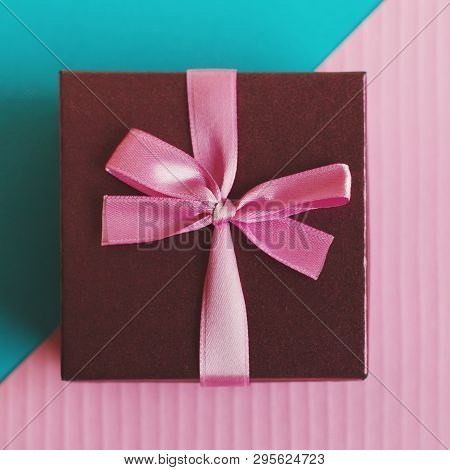 Gift Box With Small Pink Ribbon On Pink And Turquoise Background. Gifts Wrapping, Top View