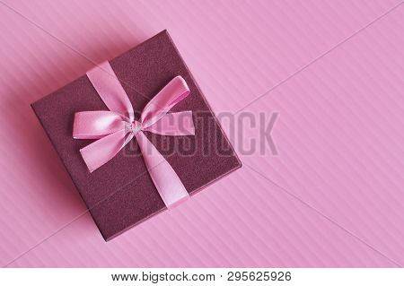 Small Purple Gift Box With Pink Ribbon On Colorful Pink Background, Top View