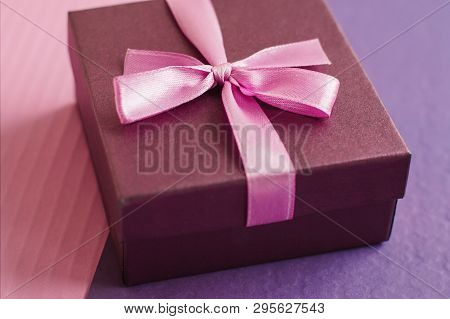Gift Box With Small Pink Bow On Pink And Purple Background