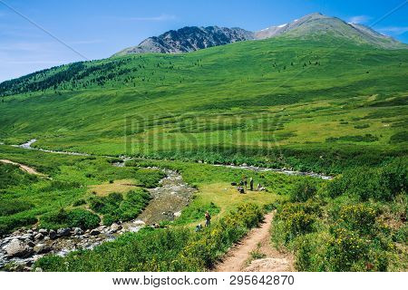 Tourists Into Wild At Rest Halt In Valley On Meadow Near Two Creek On Background Of Giant Mountains