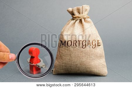 The Figure Of A Man Is Handcuffed To A Money Bag With The Word Mortgage. Impossibility Of Paying Int