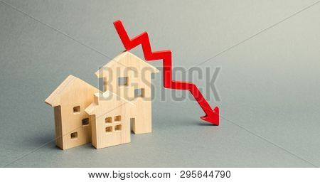 Miniature Wooden Houses And A Red Arrow Down. The Concept Of Low Cost Real Estate. Lower Mortgage In