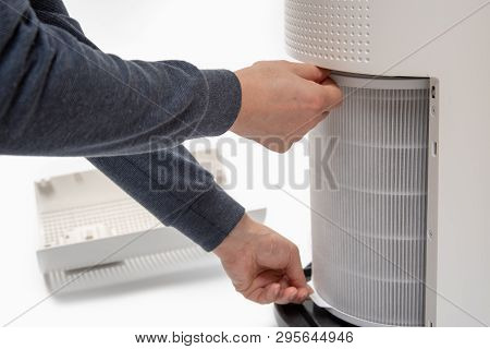 A Mans Hand Turning An Air Purifiers Filter Into A New One.