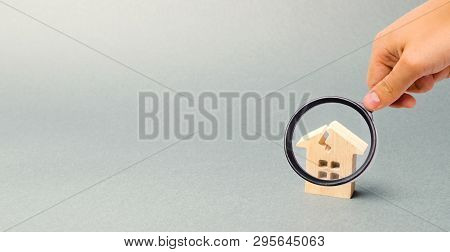 A Wooden House With A Crack. The Concept Of A Damaged House, Dilapidated Housing. Home Repair After
