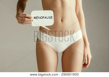 Handwriting text writing Menopause. Concept meaning cessation of menstruation. Young adult woman holding paper card for sign or symbol. Cut out part of body. Medical problem and solution. poster