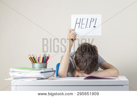 Sad Tired Frustrated Boy Sitting At The Table With Many Books And Holding Paper With Word Help. Lear