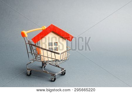 poster of Wooden house in a Supermarket trolley. The concept of buying a house or apartment. Affordable housing. Profitable and cheap loans for real estate. Buying a home. Mortgage and loan. Place for text