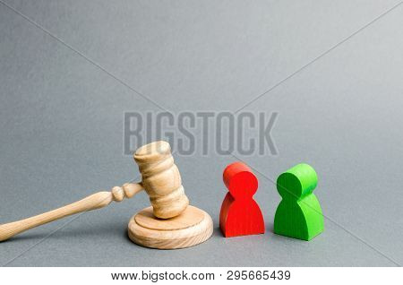 Wooden Figures Of People Standing Near The Judge's Gavel. Litigation. Business Rivals. Conflict Of I
