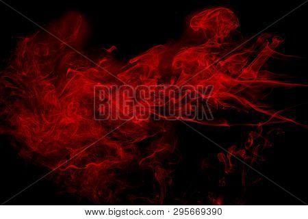 Abstract Red  Smoke On Black Background. Dramatic Red Smoke Clouds. Movement Of Colorful Smoke.