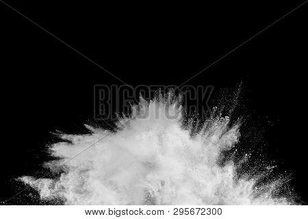 White powder explosion isolated on black background. White dust particles splash.Color Holi Festival