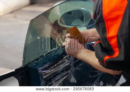 The Wizard For Installing Additional Equipment Sticks A Tint Film On The Side Front Glass Of The Car