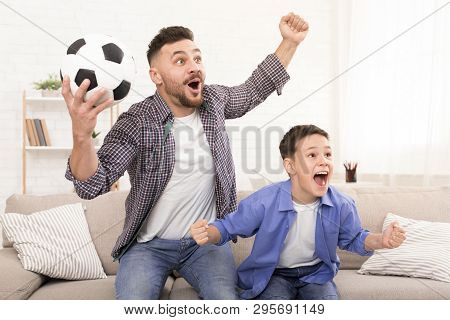 Emotional Father And Son Soccer Fans Cheering With Football Ball, Watching Sport On Tv At Home