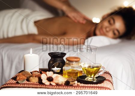 African Woman Enjoying Aromatherapy Massage In Luxury Spa With Candles On Foreground