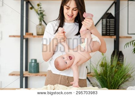 Young Mother Hold Upside Down Smiling Baby.