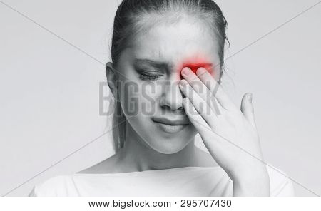 Tired Exhausted Woman Suffering From Strong Eye Pain, Touching Red Painful Eyes, Monochrome Photo