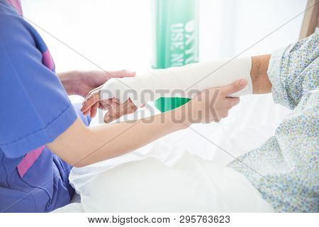 Closeup Doctor Bandaging Arm Of Senior Woman Patient In Hospital