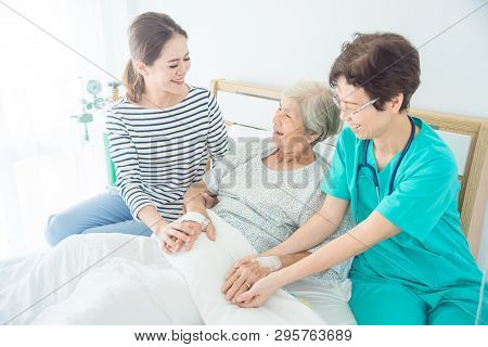 Doctor Talking To Happy Elderly Female Patient Lying In Bed While Patient's Daughter Sitting Beside