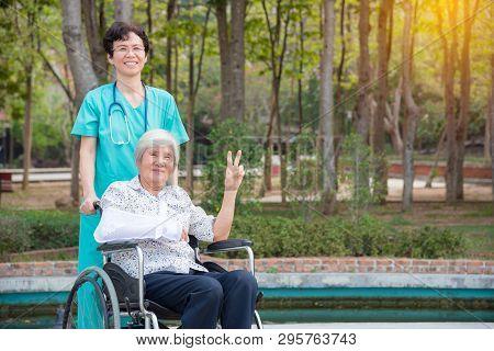Happy Asian Senior Woman On Wheelchair With Nurse In Nursing Home Hospital Garden