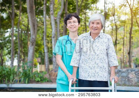 Disabled Senior Asian Woman Walking With Assistance From Nurse In Hospital Park