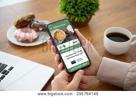 Female Hands Holding Phone With App Delivery Food On The Screen Above The Table In The Office