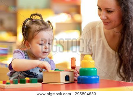 Nursery Kid Playing Developmental Toys With Mother Or Teacher Indoors
