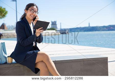 Happy Content Business Consultant Talking To Customer Outdoors. Young Woman In Formal Suit Sitting O