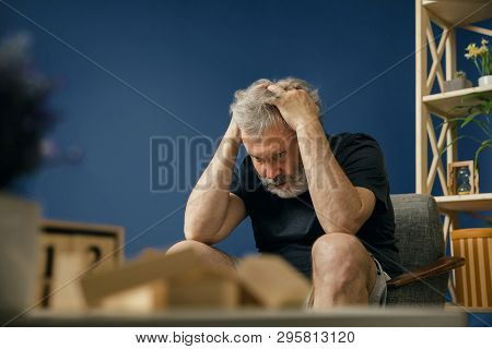 Terrible Ordeals. Old Bearded Man With Alzheimer Desease Sitting On The Chair And Suffering From Hea