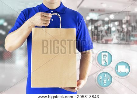 Delivery Man Hand Holding Paper Bag In Blue Uniform And Icon Media For Order Shopping Online. Delive
