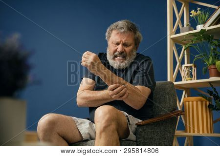 Injustice. Old bearded man sitting on the chair and suffering from pain in arm muscles on blue background. Concept of illness, diseases of the joints and bones, surgical pathology, healthcare. poster