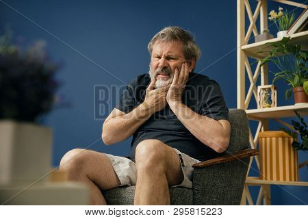 Loosing His Face And Feelings. Old Bearded Man In Black Shirt Sitting On The Chair And Suffering Fro