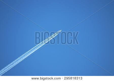 Trail Of Jet Plane On Clear Blue Sky. Airplane In The Sky With Contrail