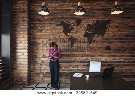 Businesswoman Checking A Handheld Journal And Mobile Phone As She Stands Alongside Her Desk In A Lar