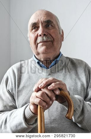 Nostalgic Elderly Man With A Walking Cane Or Stick Sitting Thinking On His Memories With A Faraway E